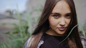 Uma jovem mulher com cabelo longo olha através da folha dos juncos à câmera filme