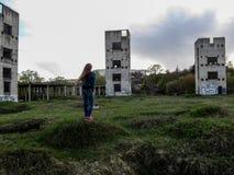 Uma jovem mulher com cabelo louro longo está na perspectiva de três torres metade-arruinadas em um dia nebuloso Imagem de Stock