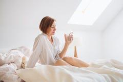 Uma jovem mulher com a camisa da noite que senta-se dentro na cama na manhã, guardando a água imagem de stock