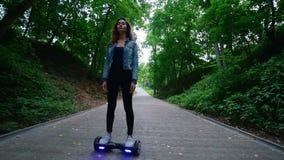Uma jovem mulher com uma figura delgada, ondas bonitas que montam um giroscópio no parque Movimento lento vídeos de arquivo
