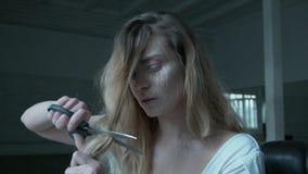 Uma jovem mulher com grandes tesouras corta seu cabelo Um louro com uma composição expressivo em sua cara faz-se um novo vídeos de arquivo