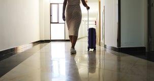 Uma jovem mulher com uma mala de viagem nas rodas escala as escadas e as caminhadas abaixo do salão a uma sala de hotel filme