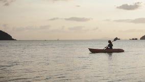 Uma jovem mulher com uma pá em suas mãos está flutuando em um caiaque video estoque