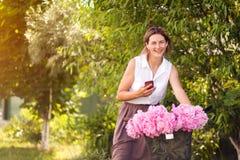 Uma jovem mulher com peônias foto de stock