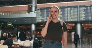 Uma jovem mulher com uma posição da trouxa na partida de espera do aeroporto que fala no telefone filme