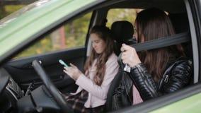 Uma jovem mulher com sua filha adolescente está passando o tempo junto A mamã pega um carro, e a filha usa um smartphone vídeos de arquivo