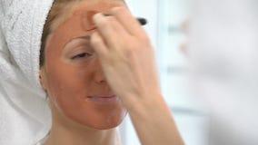 Uma jovem mulher com uma toalha branca pôs sobre sua cara uma máscara hidratando marrom video estoque