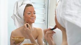 Uma jovem mulher com uma toalha branca pôs sobre sua cara uma máscara hidratando marrom filme