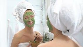 Uma jovem mulher com uma toalha branca pôs sobre sua cara uma máscara hidratando verde filme