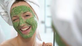 Uma jovem mulher com uma toalha branca pôs sobre sua cara uma máscara hidratando verde video estoque