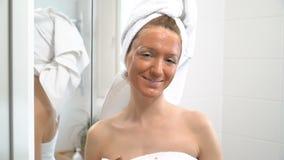 Uma jovem mulher com uma toalha branca pôs sobre sua cara um mas hidratando marrom vídeos de arquivo