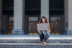 Uma jovem mulher com um portátil que senta-se nas escadas, perto do univ Imagens de Stock