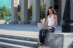 Uma jovem mulher com um portátil que senta-se nas escadas, perto do univ Fotografia de Stock Royalty Free