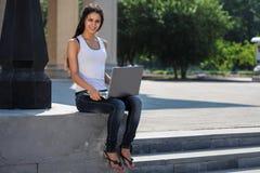 Uma jovem mulher com um portátil que senta-se nas escadas, perto do univ Imagens de Stock Royalty Free
