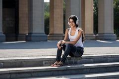 Uma jovem mulher com um portátil que senta-se nas escadas, perto do univ Foto de Stock Royalty Free