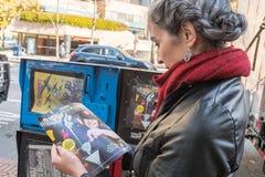 Uma jovem mulher consulta um guia do happy hour em Seattle fotografia de stock