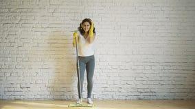 Uma jovem mulher da dança que limpa uma mulher em risos amarelos das luvas, posses um espanador em suas mãos vídeos de arquivo