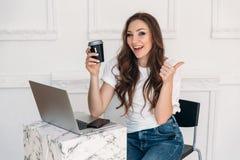 Uma jovem mulher de brilho lindo que senta-se em um café, em um café bebendo e mostrando seu polegar acima A menina está trabalha Fotografia de Stock