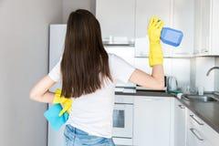 Uma jovem mulher de uma empresa de limpeza profissional limpa em casa Um homem lava a cozinha em luvas amarelas com imagens de stock