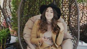 Uma jovem mulher de sorriso bonita que veste um revestimento e um chapéu negro em sua cabeça está sentando-se em uma cadeira em u vídeos de arquivo