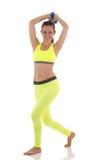 Uma jovem mulher de sorriso descalça bonita moreno no amarelo brilhante ostenta o sutiã e a calças que fazem exercícios para o co imagem de stock