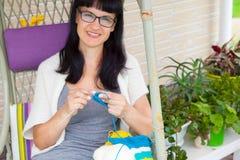 Uma jovem mulher de sorriso faz malha as peúgas feitas malha com woole colorido imagem de stock
