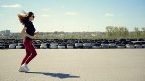 Uma jovem mulher delgada corre através do quadrado contra o contexto das rodas de carro dobradas Movimentar-se da manhã de um act filme