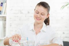 Uma jovem mulher derrama a água foto de stock