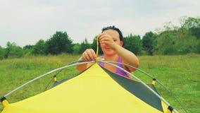 Uma jovem mulher desata a barraca da barraca dos arcos para prender vídeos de arquivo