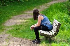 Uma jovem mulher descansa em um banco como ventos de uma fuga em torno dela Fotos de Stock