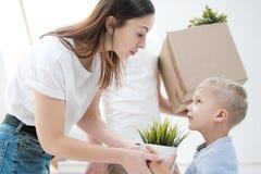 Uma jovem mulher e uma criança estão guardando uma caixa de cartão com coisas em um fundo branco foto de stock