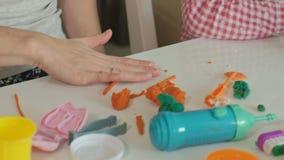 Uma jovem mulher e um molde da menina seus dentes do plasticine, introduzem seus dentes em uma maxila do brinquedo, cintas ajusta video estoque