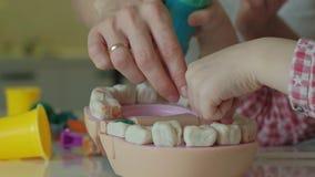 Uma jovem mulher e um molde da menina seus dentes do plasticine, introduzem seus dentes em uma maxila do brinquedo, a menina fura vídeos de arquivo