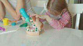Uma jovem mulher e um molde da menina seus dentes do plasticine, introduzem seus dentes em uma maxila do brinquedo, removem as ci vídeos de arquivo