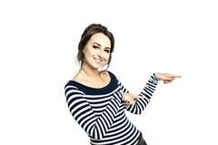 Uma jovem mulher em uma blusa apertada listrada mostra com dois dedos um gesto ao lado, à direita fotografia de stock royalty free