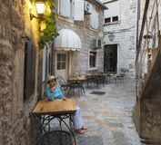 Uma jovem mulher em uma blusa brilhante de turquesa senta-se em uma tabela de um café da rua imagens de stock