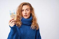 Uma jovem mulher em uma camiseta é surpreendida pelo dinheiro, um hryvnia, o Foto de Stock