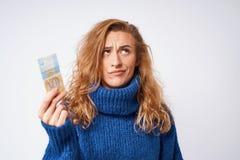 Uma jovem mulher em uma camiseta é surpreendida pelo dinheiro, um hryvnia, o Imagens de Stock