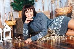 Uma jovem mulher em uma camiseta longa morna cinzenta na decoração do ` s do ano novo em um assoalho de madeira marrom Fotografia de Stock Royalty Free