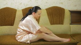 Uma jovem mulher em casa no sofá aplica o talco na pele de seus pés após a depilação vídeos de arquivo