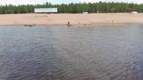 Uma jovem mulher em corridas de um vestido ao longo da praia Tiro a?reo filme