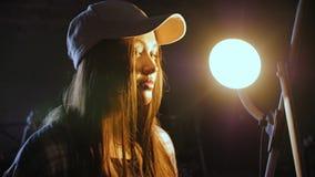 Uma jovem mulher em um boné de beisebol, com o cabelo longo que está no meio de uma oficina de reparações do carro video estoque