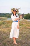 Uma jovem mulher em um branco longo bordou a camisa e em uma grinalda Imagem de Stock Royalty Free
