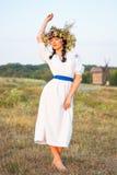 Uma jovem mulher em um branco longo bordou a camisa e em uma grinalda Fotografia de Stock