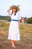 Uma jovem mulher em um branco longo bordou a camisa e em uma grinalda Imagens de Stock Royalty Free