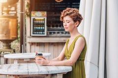 Uma jovem mulher em um café bebendo do vestido em um café do verão Foto de Stock Royalty Free