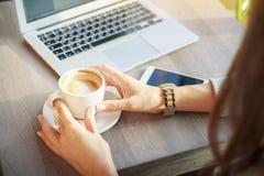 Uma jovem mulher em um café está guardando uma xícara de café Uma menina trabalha Imagens de Stock