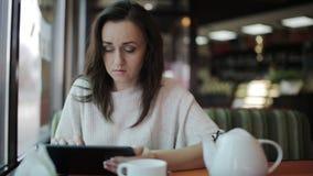 Uma jovem mulher em um café usa uma tabuleta para trabalhos em rede e o email sociais filme
