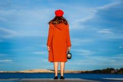 Uma jovem mulher em um casaco está para trás e olha o mar azul imagem de stock