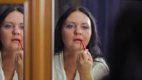 Uma jovem mulher em um revestimento branco na frente de um espelho cerca o contorno de seus bordos com um lápis vermelho filme